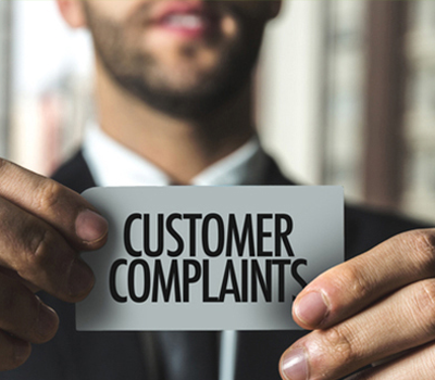 Man holding consumer complaints sign